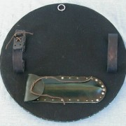 Close up of the back of a HF1002 Fighting Targe, showing the arm grips, display ring, and spike transport pouch.