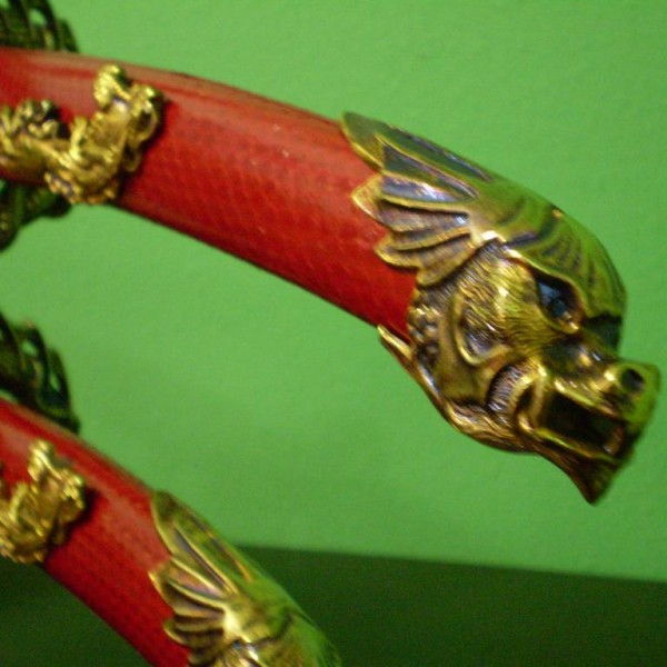 The flying dragon motif is repeated in the pommel and guards of both swords.