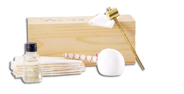 Aka 1003-GT, the kit contains blade oil (traditional choji oil), rice papers, an oiling cloth, a powder ball for blade polishing, a brass awl and hammer, and saya shimming veneer. The kit is contained in a fitted wooden box.